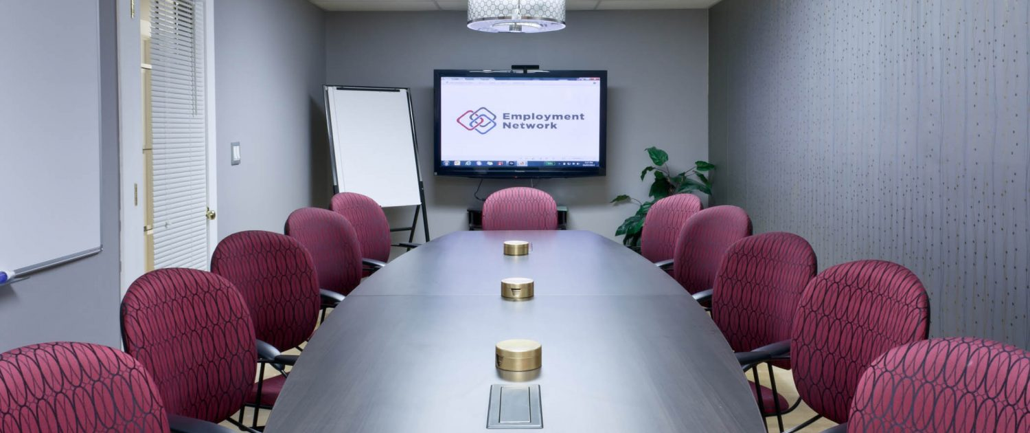 long shot of boardroom table surrounded by red chairs tv on far wall